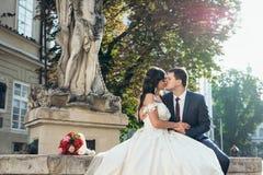Portrait horizontal en buste des couples heureux de mariage embrassant sur les vieilles fontaines au fond du coucher du soleil Image stock