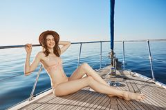 Portrait of hot attractive adult female, sitting on bow of yacht, winking to camera in bikini and straw hat. Cute woman Royalty Free Stock Photo