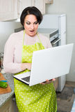 Portrait of  housewife in apron with laptop at kitchen Stock Image