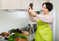Portrait of housewife in apron making selfie in domestic kitchen Stock Image