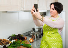 Portrait of housewife in apron making selfie in domestic kitchen Stock Images