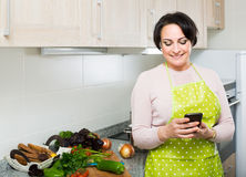 Portrait of  housewife in apron receiving sms with recipe Royalty Free Stock Photo