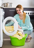 Portrait of housewife with bed linen near washer Royalty Free Stock Images