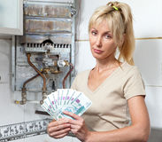 Portrait housewife counts up money for repair of a gas water heater Stock Photography