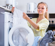Portrait of  housewife taking clothes out washing machine Royalty Free Stock Photo