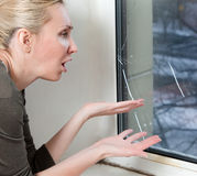 Portrait  housewife at the window which have burst from a frost with a double-glazed window Royalty Free Stock Photo
