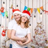 Portrait of hugging beautiful young couple in red hats Stock Photography