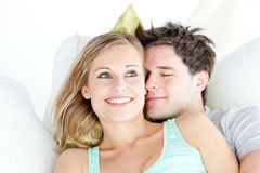 Portrait of a hugging couple lying on a sofa Stock Photos