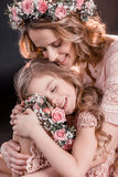 Portrait of hugging daughter and mother with flowers wreathes. On black Stock Photos