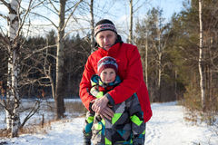 Portrait of hugging mature father and son in warm clothes are in winter forest Royalty Free Stock Image