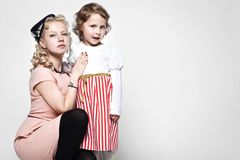 Portrait of a hugging mother and daughter dressed in beautiful dresses in retro style. Portrait of hugging mother and daughter dressed in beautiful dresses in Royalty Free Stock Photos