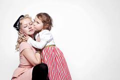 Portrait of a hugging mother and daughter dressed in beautiful dresses in retro style. Portrait of hugging mother and daughter dressed in beautiful dresses in Royalty Free Stock Images