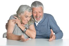 Portrait of hugging senior couple sitting at table Royalty Free Stock Image