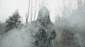 Portrait of human in gas mask standing on old railway in clouds of toxic smoke