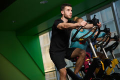 Portrait of humans on simulators. In sportswear in gym Stock Photography