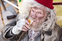 Portrait of a hungry homeless man. Delicious bread. Portrait of a hungry homeless man eating bread while looking at you Royalty Free Stock Photography
