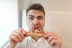 Portrait of hungry man with a piece of pizza in his hands. The man eats a pizza and looks at the camera. Stock Images