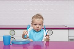 Portrait Of Hungry todler in a blue bib with fork and knife in his hands In High Chair in the modern kitchen ready to Stock Photo