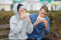 Portrait of a hungry young couple who eat burgers in the park on a bench. royalty free stock photo