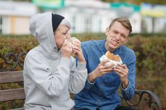 Portrait of a hungry young couple who eat burgers in a park on a bench and smiling. royalty free stock image