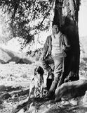 Portrait of hunter and dog under tree Royalty Free Stock Images