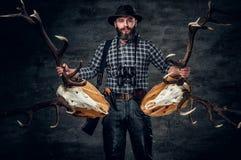 Portrait of hunter man. Holds a deer`s skull Stock Image
