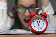 Portrait of hurried young businesswoman ooking at red retro styled clock stock photos