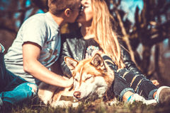 Portrait of husky dog outdoor with kissing couple behind Royalty Free Stock Photo