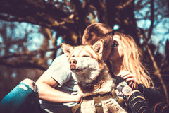 Portrait of husky dog outdoor with kissing couple behind Royalty Free Stock Photography