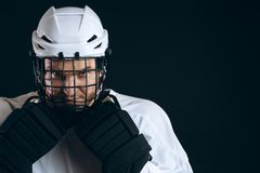 Portrait of ice-hockey player with hockey stick and protective gloves stock photography