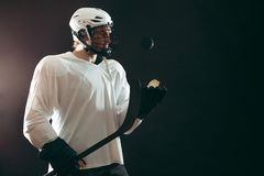 Portrait of ice-hockey player with hockey stick and puck isolated over black