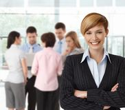 Portrait if happy businesswoman with colleagues. Working in background stock image