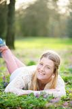 Portrait if a happy woman lying on grass outdoors Stock Photo
