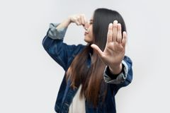 Portrait of ignoring brunette asian young woman in casual blue denim jacket with makeup standing pinching her nose and showing. Stop gesture hand. indoor studio stock photos