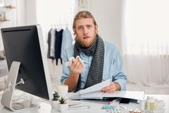 Ill bearded man sneezes, uses handkerchief, feels unwell, has flu. Sick male office worker has fever and tired Stock Image