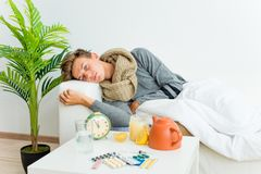 Guy having flu. A portrait of an ill guy having flu at home stock image