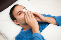 Portrait of an ill man blowing his nose Royalty Free Stock Photos