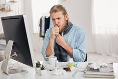 Portrait of ill sick bearded male manager coughs, has cold and flu. Young fair-haired man has running nose, cough and. Bad cold, sits at workplace in front of Stock Images