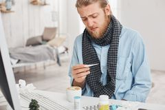 Ill or sick bearded male uses thermometer to measure temperature of his body. Fair-haired man desperately looks at royalty free stock photography