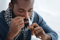 Portrait of an ill young man with nasal drops. Important liquid. Unemotional young man looking concentrated while curing his flu with a help of nasal drops Stock Image