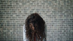 Portrait of ill young woman sneezing looking at camera on brick wall background. Portrait of ill young woman sneezing looking at camera standing on gray brick stock video footage