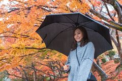 Beautiful asian woman standing in the rain with red and orange tree leaves in autumn background stock photo