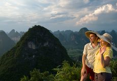 Portrait image of lovely couple at sunset on top o. F the Chinese mountain of Moon Hill. Wearing Chinese hats, looking at the sun. Guilin, Yangshuo, China, Asia royalty free stock photography