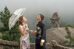 Portrait image of lovely couple with umbrella at cloudy weather Stock Images