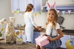 Eager little girl opening gift on easter. Portrait of impatient child resting in the cuisine with the holiday present in hands. Mom is cooking on background Royalty Free Stock Images