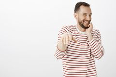 Portrait of impatient pleased cute gay boyfriend in striped shirt, blushing while man making proposal, chuckling from royalty free stock photos