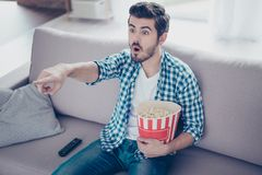 Portrait of impressed man in checkered shirt eating popcorn while watching films on tv at home and having fun royalty free stock photos