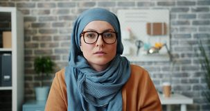 Portrait of independent Muslim girl in hijab glasses looking at camera in office. Portrait of independent young Muslim girl in hijab and glasses looking at stock footage
