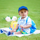 Portrait of indian baby boy with backpack sitting on ground Royalty Free Stock Image
