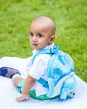 Portrait of indian baby boy with backpack sitting on ground stock photography